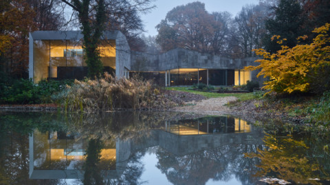 Forest house of stone and glass is reflected back in water 石頭和玻璃的森林房屋在水中反射回來